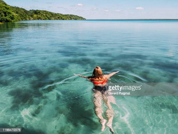 woman swimming in the clear waters of bacalar lake in a sunny day next to the lakefront - gerard puigmal stock pictures, royalty-free photos & images