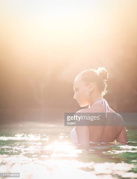 Woman swimming in the lake during sunset