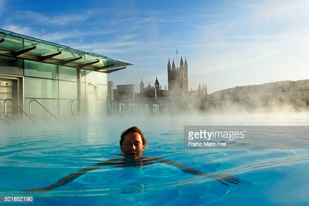 A woman swimming in the rooftop swimming pool at the roman bath, Bath