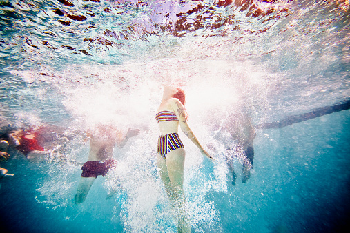 Woman swimming to surface of pool underwater view - gettyimageskorea