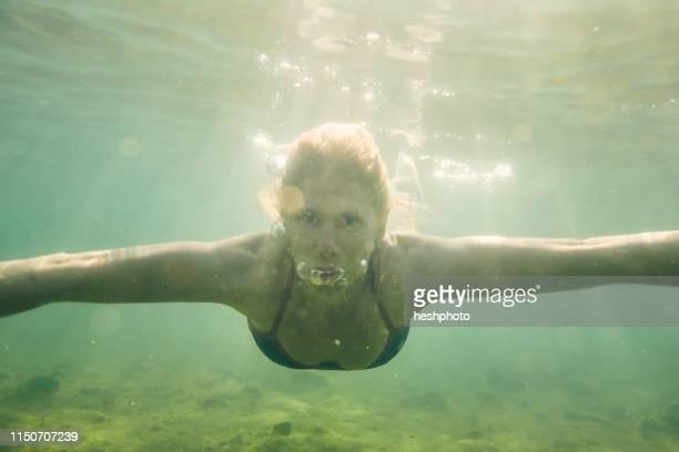 woman swimming underwater - heshphoto photos et images de collection
