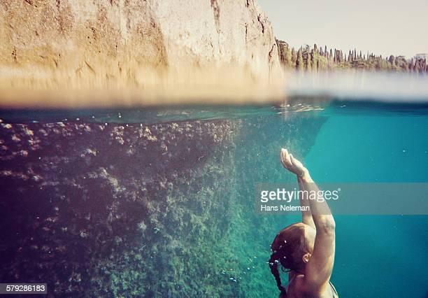 Woman swimming underwater, Sea
