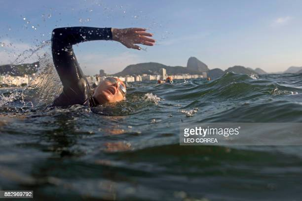 A woman swims in Copacabana beach backdropped by the Sugar Loaf mount during an open water swimming class in Rio de Janeiro Brazil on November 30...