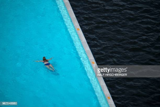 A woman swims in the Badeschiff a barge that functions as a floating swimming pool on the river Spree on May 24 2018 in Berlin where temperatures up...