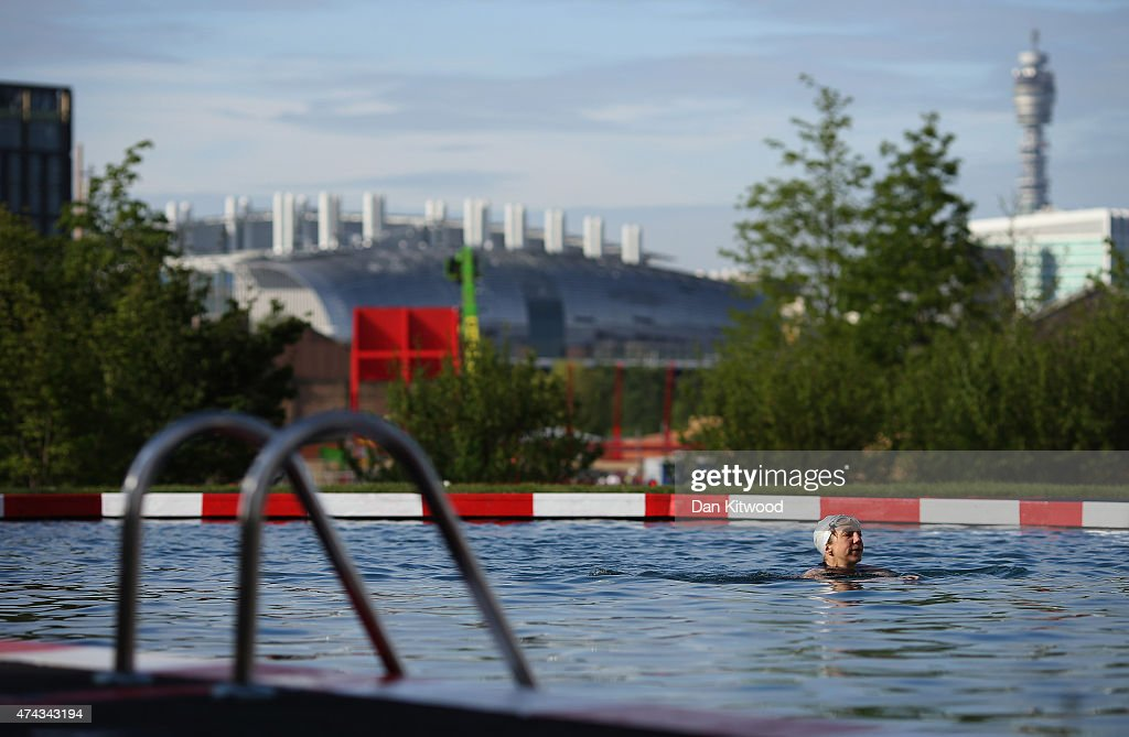 A woman swims in the new 'King's Cross Pond Club' outdoor swimming pool on May 22, 2015 in London, England. The 40 metre pool is purified using submerged plants to filter the water and is surrounded by flowers and plants. It is open to members of the public Monday and Friday between 6am and dusk.