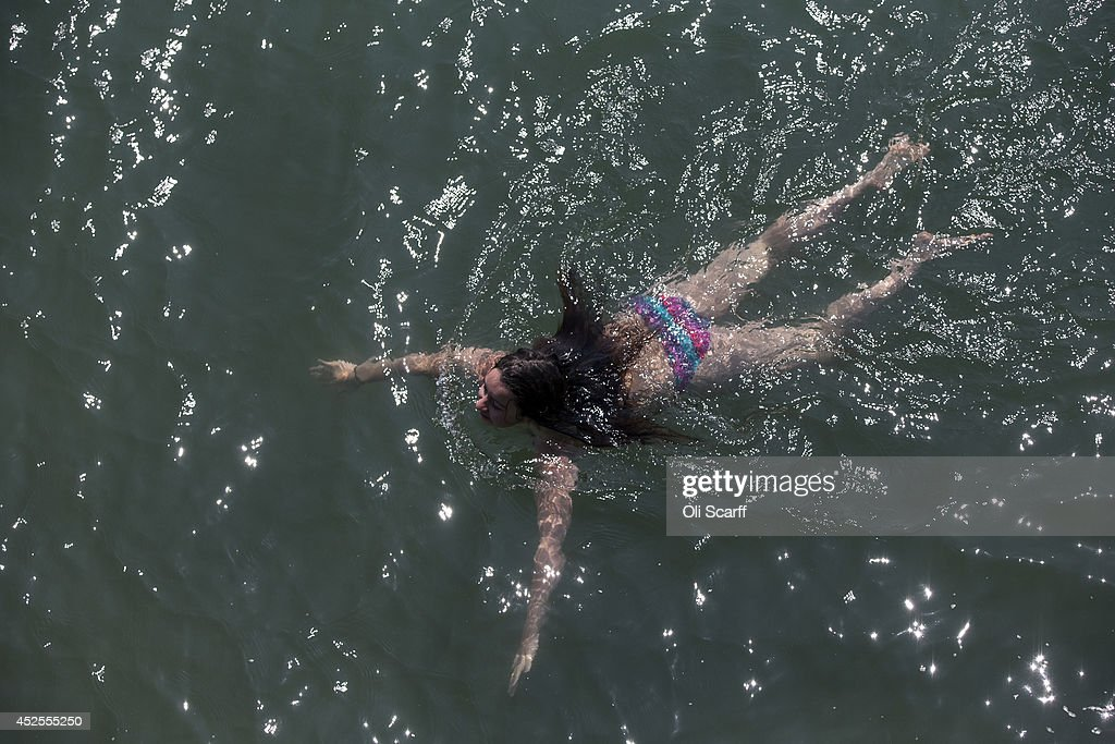 A woman swims in warm water at Brighton beach on July 23, 2014 in Brighton, England. The warm weather that large parts of the UK has experienced, is forecast to continue for the remainder of this week.
