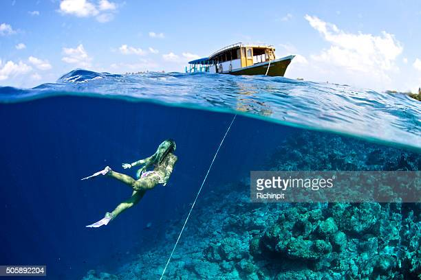 woman swims towards boat from the anchor - see through swimsuit stock photos and pictures