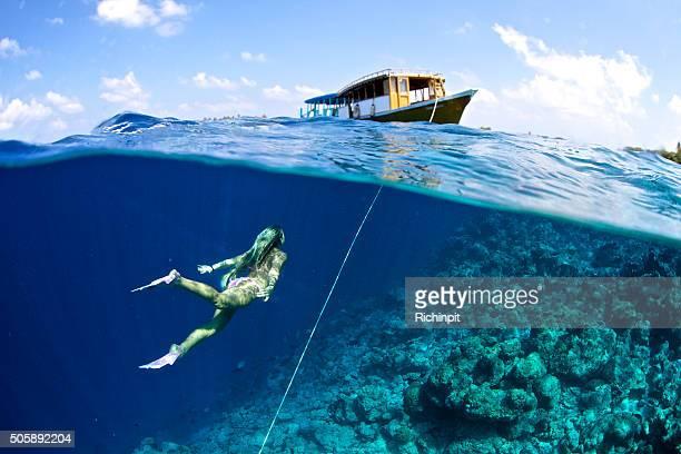Frau schwimmt in einem Boot vom Anker