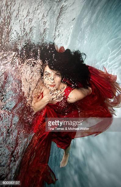 Woman swims underwater. She wears a red dress.