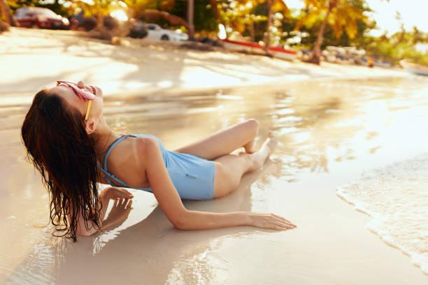Woman swimwear relaxing on a golden beach.