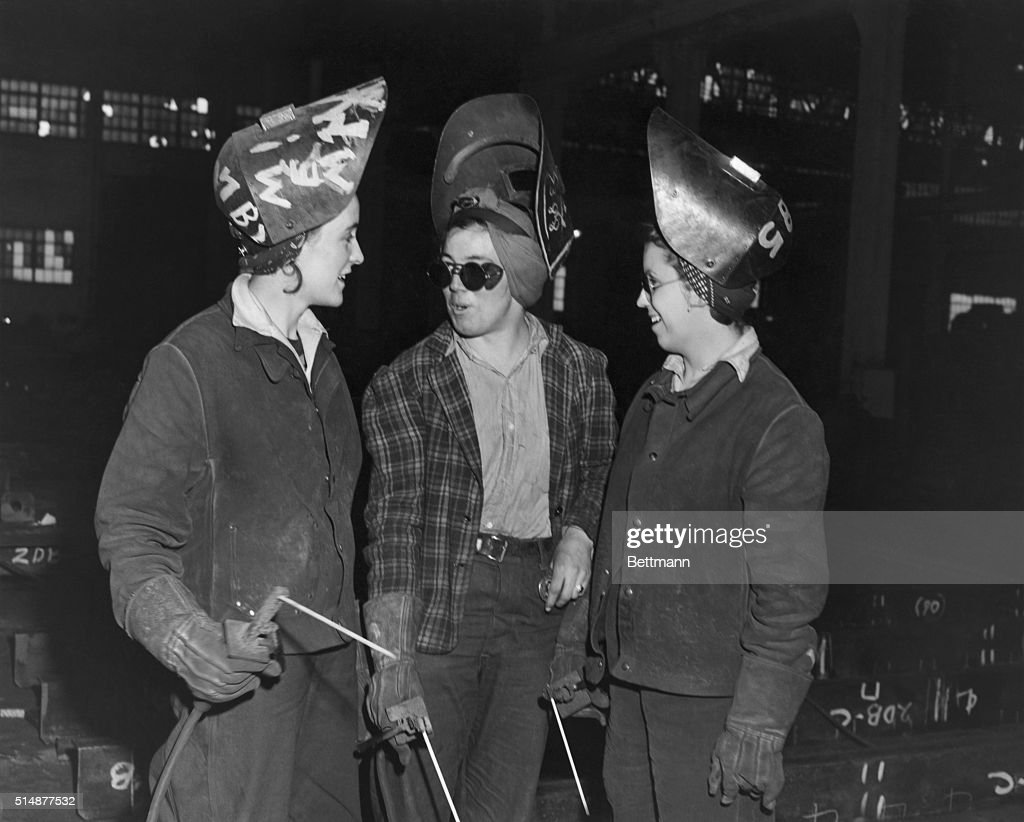 Woman swing shifters interrupting their work as welders at Bethlehem Steel Shipyard for chat. World War II photograph.