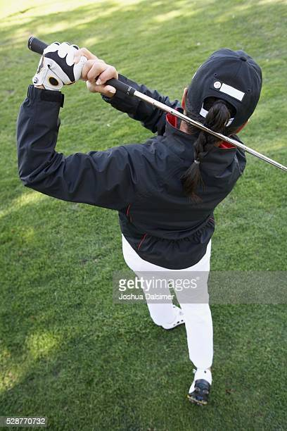 Woman Swinging a Golf Club