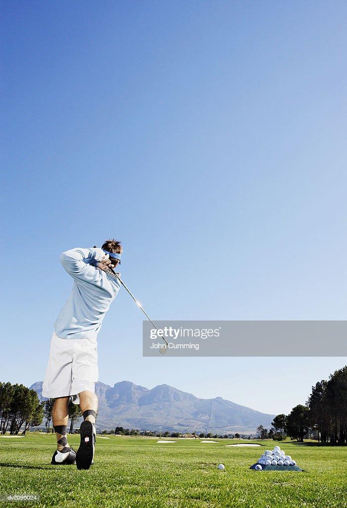 Woman Swinging a Golf Club : Stock Photo