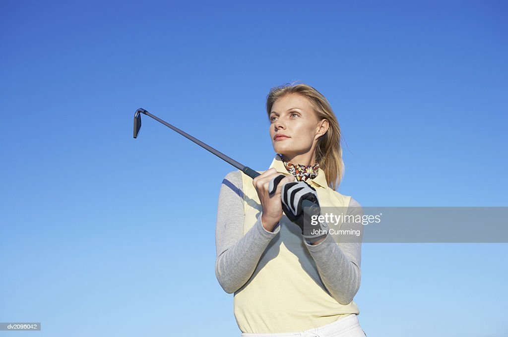 Woman Swinging a Golf Club : Stock Photo