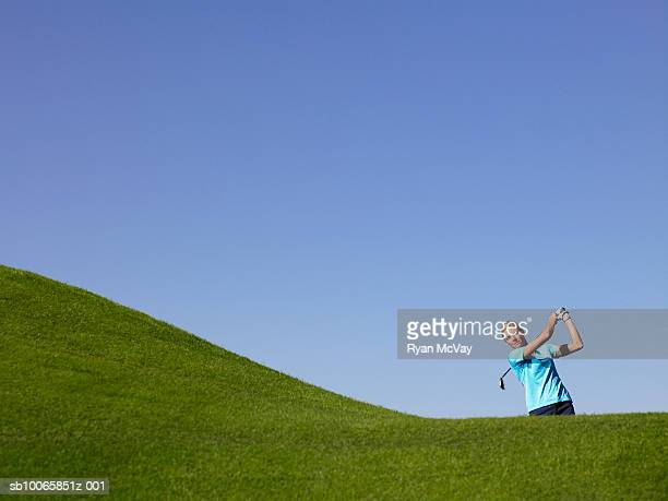 Woman swinging at golf course