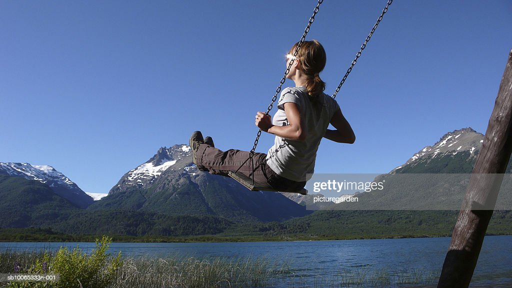 Woman swinging by lake, snowcapped mountains in background : Foto stock