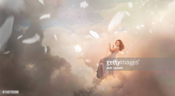 Woman swinging in sky with falling feathers