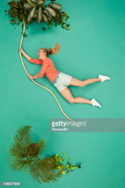 Woman swinging on a liana through the jungle
