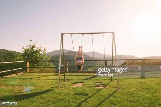 Woman swinging on a swing on the mountain during sunset
