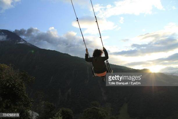 Woman Swinging On Mountain Against Sky