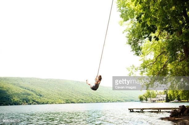 woman swinging on rope over lake against clear sky - spielgerät stock-fotos und bilder