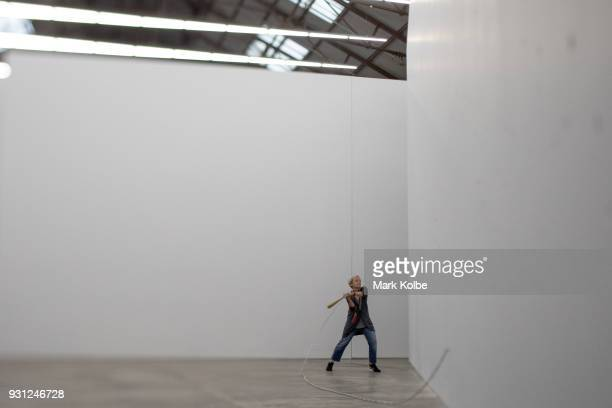 A woman swings a baseball bat at the wall as she interacts with the artwork 'Constellations' by artist Marco Fusinato which is part of the 31st...