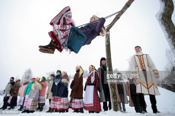 TOPSHOT A woman swings as people celebrate Shrovetide in the village of Krevo some 100km northwest of Minsk on February 17 2018 Shrovetide is an...