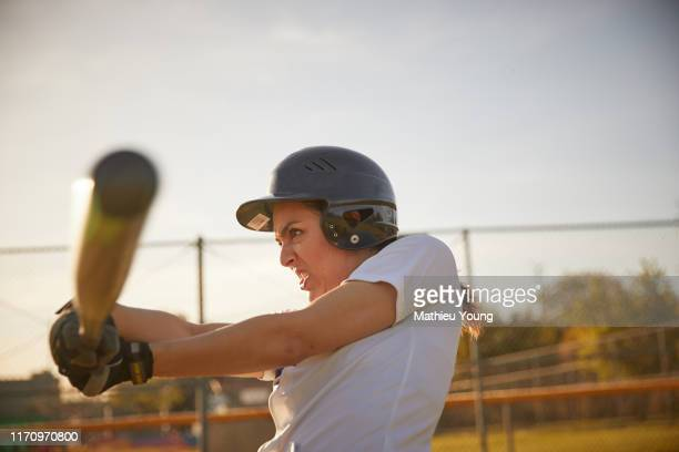 Woman swings baseball bat