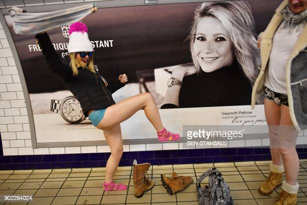 A woman swings her trousers in the air as she undresses to take part in the annual 'No Trousers On The Tube Day' on the Central line in London on...