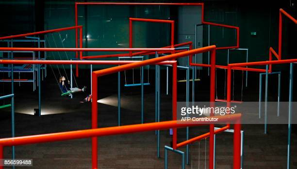 A woman swings on a piece of art part of a largescale installation entitled One Two Three Swing by Danish Collective Superflex during a photocall for...
