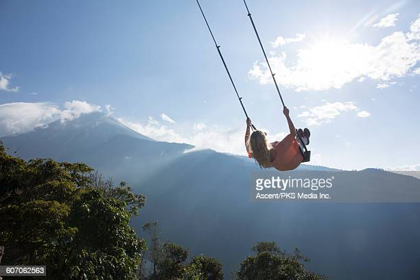 Woman swings out over valley, volcano behind