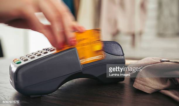 woman swiping credit card through credit card reader - credit card reader stock pictures, royalty-free photos & images