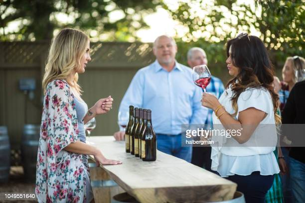 Woman Swirling Wine with Sommelier Explaining