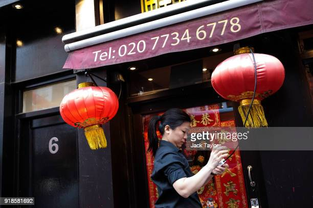 Woman switches on lanterns outside a restaurant in Chinatown ahead of Chinese New Year tomorrow on February 15, 2018 in London, England. Chinese New...