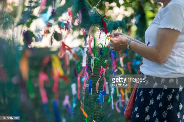 A woman symbolically ties a ribbon onto a piece of netting during a 'Great Get Together' community service and picnic in memory of Jo Cox marking the...