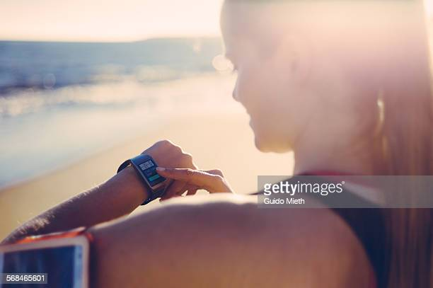 Woman synchronizing smartwatch and mobile phone.