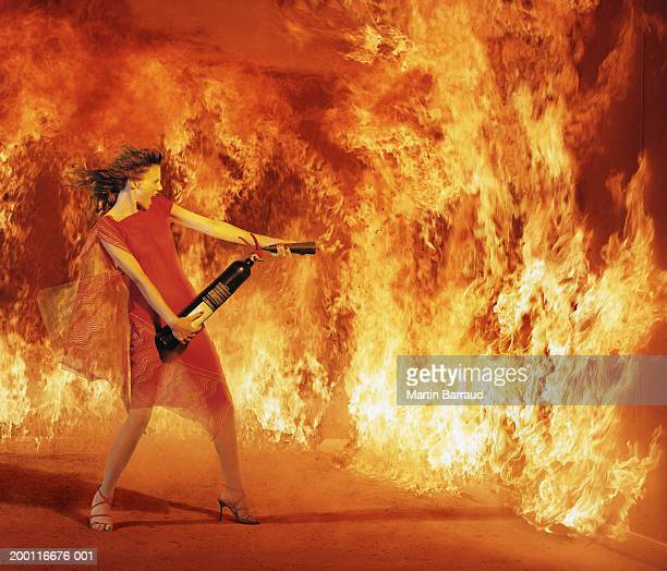 woman tackling fire with hand held extinguisher (digital composite) - fire extinguisher stock pictures, royalty-free photos & images