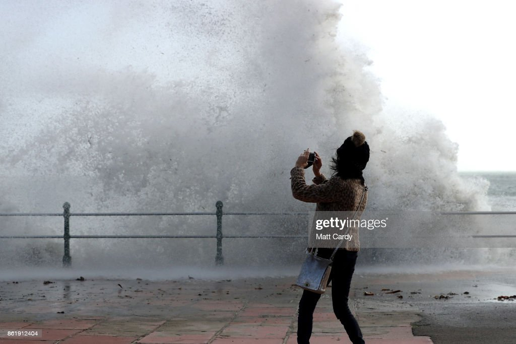 A woman take a photograph as waves crash up onto Penzance seafront on October 16, 2017 in Cornwall, England. The hurricane comes exactly 30 years after the Great Storm of 1987 which killed 18 people and is estimated to have caused £1bn in damage to property and infrastructure.