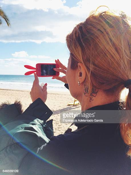 Woman take a picture with smartphone in Benidorm Spain