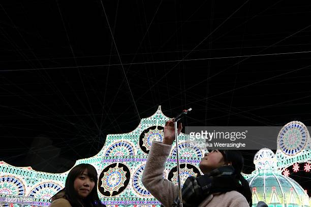 A woman take a selfie under an illuminated structure as a part of the 21th Kobe Luminarie on December 4 2015 in Kobe Japan This annual event...