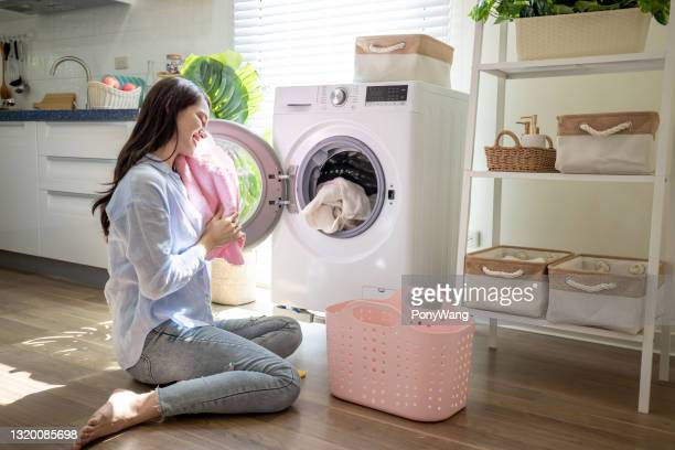 woman take clothes from washer - washing machine stock pictures, royalty-free photos & images