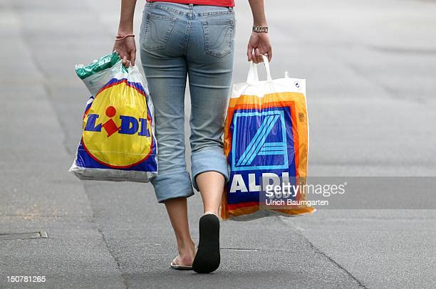 Woman take shopping bags of Lidl and Aldi