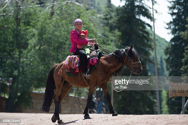 A woman takes a baby and rides on a horse at Qiong Ku Shi Tai Village in Yili Xinjiang Uyghur Autonomous Region northhwest China on 8th June 2015