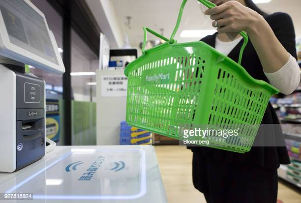 A woman takes a basket of items with radiofrequency identification tags to an unmanned cash register during a demonstration at a FamilyMart UNY...