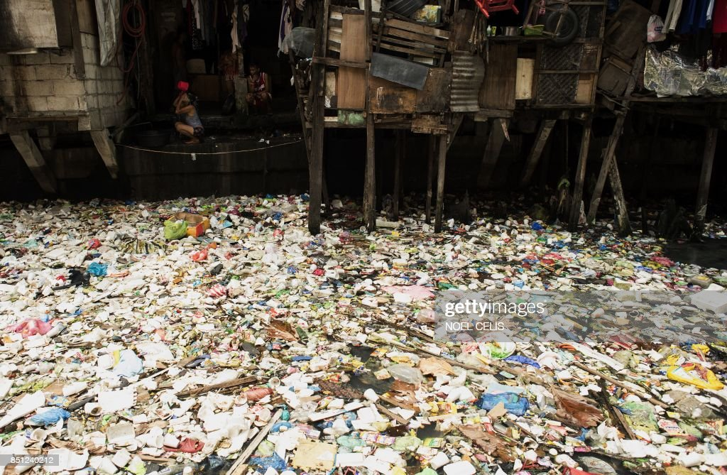 A woman takes a bath beside a garbage filled creek in Manila on September 22, 2017. Giant Western consumer products brands led by Nestle, Unilever and Procter & Gamble cause serious ocean pollution by packaging products sold in the Philippines in cheap and disposable plastics, Greenpeace alleged on September 22. The environmental watchdog group ranked the Philippines as the 'third worst polluter into the world's oceans' behind China and Indonesia in a report released in Manila. /