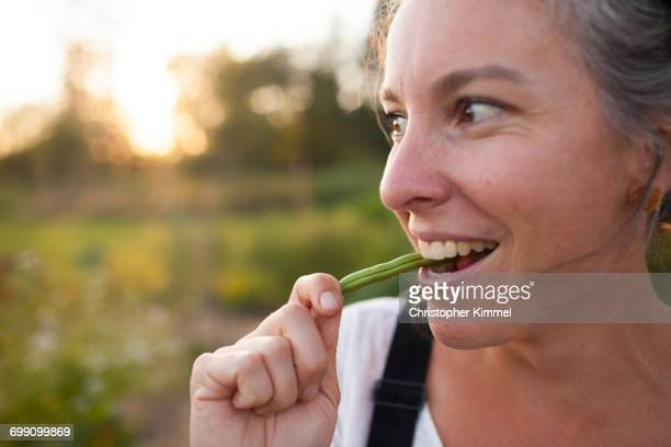 A Woman Takes A Bite Of A Freshly Picked Bean While Gardening In Fort Langley