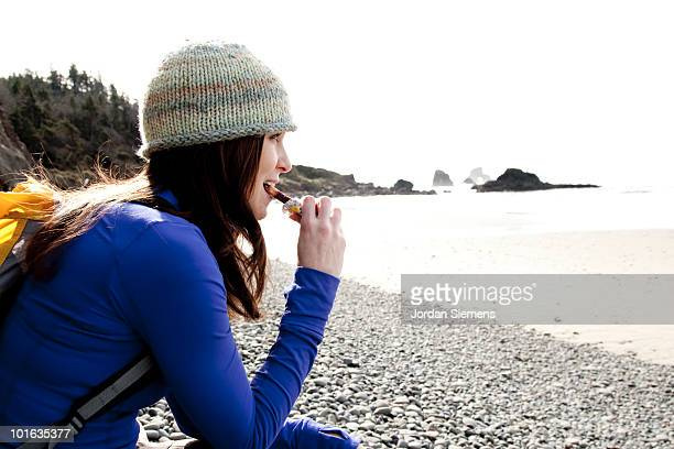Woman takes a break from hiking to eat and rest.