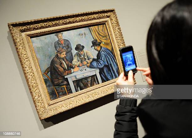 A woman takes a cell phone photograph of Paul Cézanne's 189092 The Card Players on February 7 2011 at the Metropolitan Museum of Art in New York...