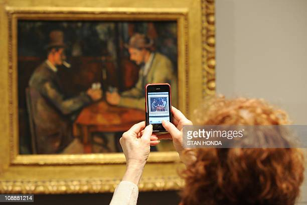 A woman takes a cell phone photograph of The Card Players 189296 by Paul Cézanne on February 7 2011 at the Metropolitan Museum of Art in New York...