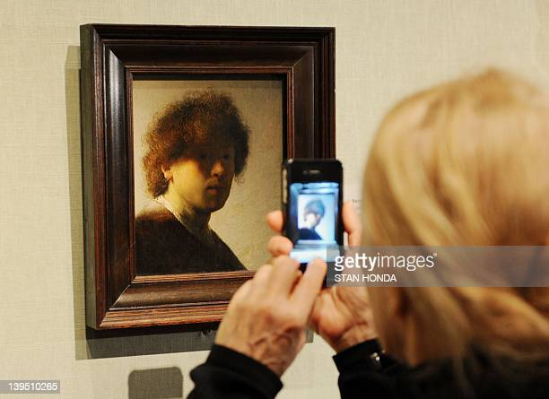 A woman takes a cellphone photograph of SelfPortrait as a Young Man 162829 by Rembrandt van Rijn in the exhibition Rembrandt and Degas Portrait of...